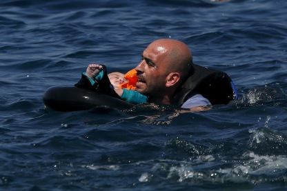 A Syrian refugee holding a baby in a lifetube swims towards the shore after their dinghy deflated some 100m away before reaching the Greek island of Lesbos, September 13, 2015. Of the record total of 432,761 refugees and migrants making the perilous journey across the Mediterranean to Europe so far this year, an estimated 309,000 people had arrived by sea in Greece, the International Organization for Migration (IMO) said on Friday. About half of those crossing the Mediterranean are Syrians fleeing civil war, according to the United Nations refugee agency. REUTERS/Alkis Konstantinidis - RTSUN7